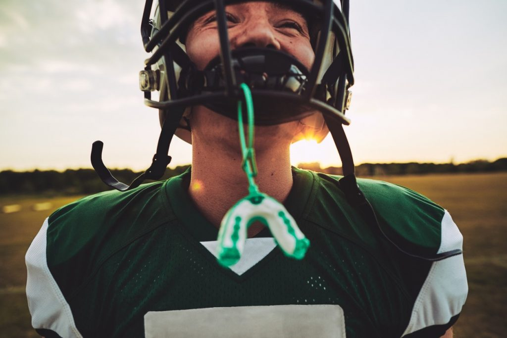 football player showing mouthguard for sports protection